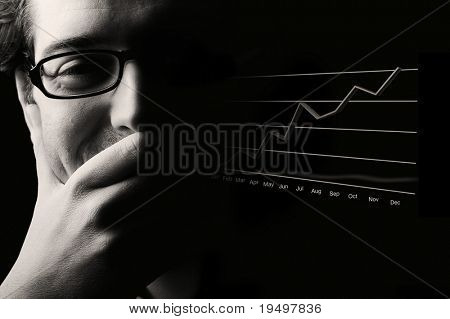 Close-up of content male professional being happy about prosperous business outlook, low- key black & white image.
