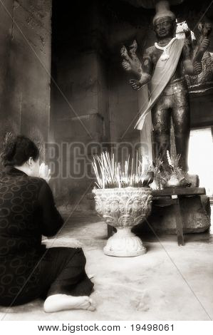 Asian woman paying to Vishnu statue  at Angkor Wat temple, Angkor, Cambodia, infrared-monochrome image.