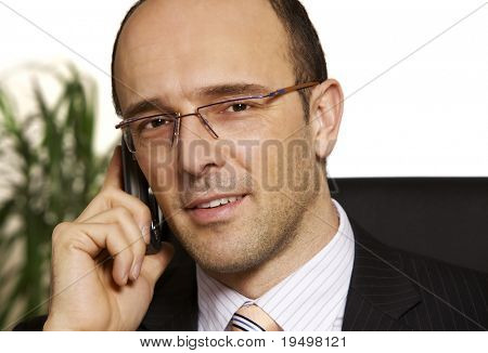 Friendly businessman in suit sitting at desk in office talking on cell phone, white background