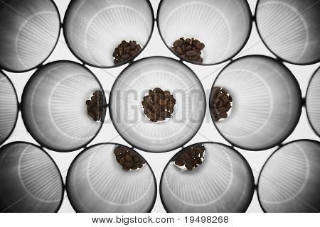 Small portions of roasted coffee beans in an symmetrical arrangement of plastic cups forming a background pattern, top view