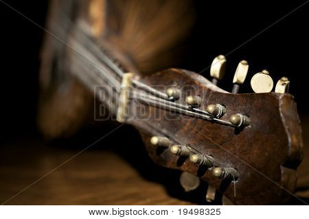Closeup of old mandolin lying on wooden board and black background.
