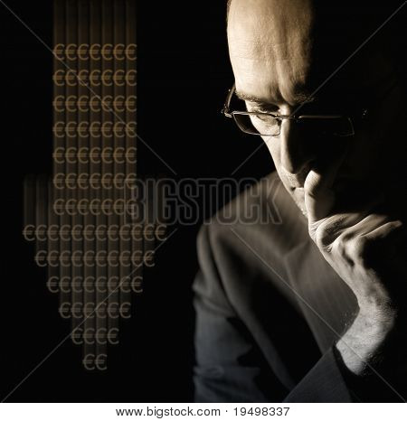 Portrait of businessman in suit worried about Euro currency depreciation, low-key image.