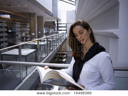 Young attractive woman standing at handrail in modern university library reading a book.