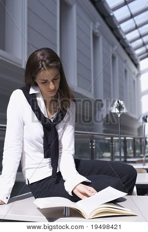 Pretty young woman sitting on desk in modern university library reading a book.
