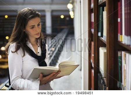 Young attractive woman standing at bookshelf in old university library reading a book.