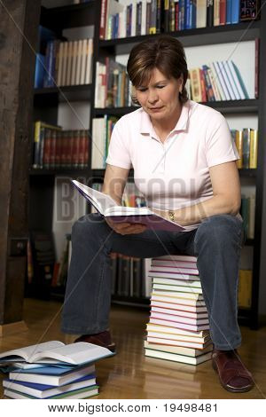 Friendly senior woman sitting on book stack in front of bookshelf at home and reading a book.