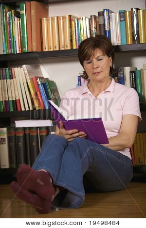 Friendly senior woman sitting on floor in front of bookshelf at home and reading a book.