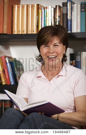 Laughing senior woman sitting on floor in front of bookshelf at home and reading a book.