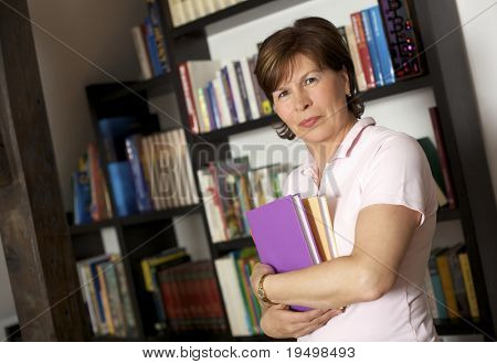 Friendly senior woman standing in front of bookshelf at home and carrying books.