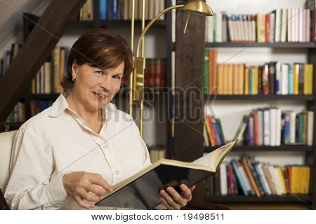Cheerful senior woman sitting in chair at home in front of bookshelves reading a book.