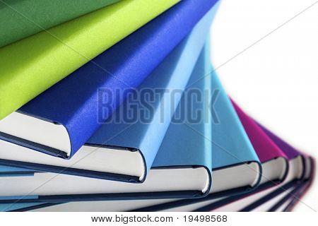 Close-up of winding stack of multi-colored real books on white background, side view.