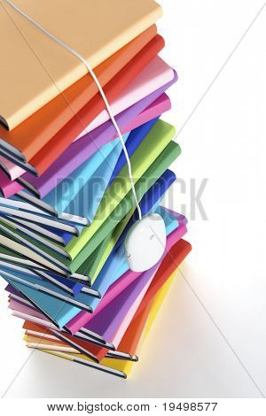E-learning concept - computer mouse hanging from top of stack of colorful real books on white background, tilted view.