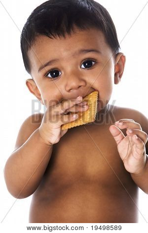 Beautiful sweet Indian baby with big eyes eating a cookie, isolated on white background.
