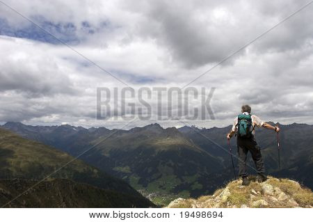 Active senior hiker standing at summit with hiking sticks and rucksack enjoying the stunning landscape of the Alps, Tyrol, Austria.