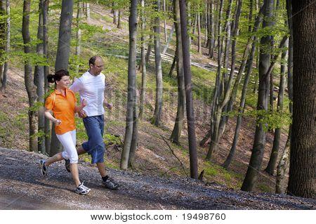 Paar jogging auf Kiesweg nebeneinander mit Buchenwald im Hintergrund.