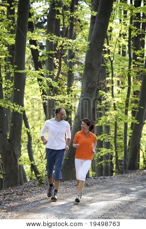 Happy couple jogging together on gravel path in beech forest.