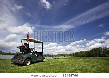 Golf buggy driving on beautiful golf course with lake and fairway and beautiful cloud formation.