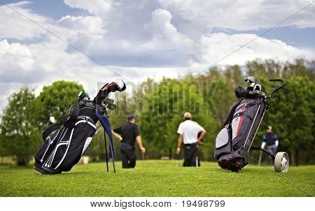 Dois sacos de golfe em pé na frente de um grupo de jogadores de golfe colocando em verde.