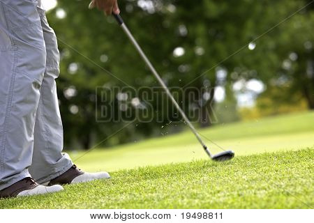 Golf player pitching the golf ball onto the green, ball in the air.