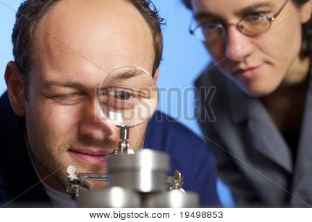 Close-up of young male engineer in blue overall looking through magnifying glass at metal parts and assistant in background watching him, isolated on blue background.