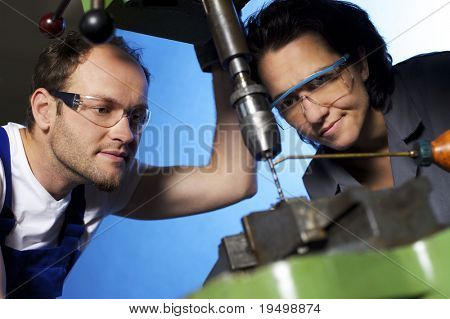 Close-up of young technicians in blue and grey overall working on pillar drilling machine in workshop, blue background, focus on people.