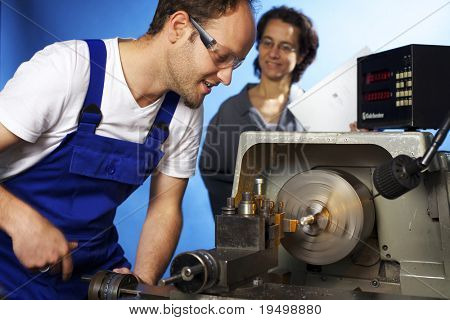 Young male technician in blue overall working on lathe machine in workshop with co-worker watching him, isolated on blue background.