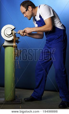 Young male technician in blue overall working on grinding bench in workshop, blue background.