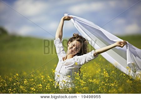 Young smiling woman standing in yellow rapeseed field holding a white long piece of cloth in the wind.