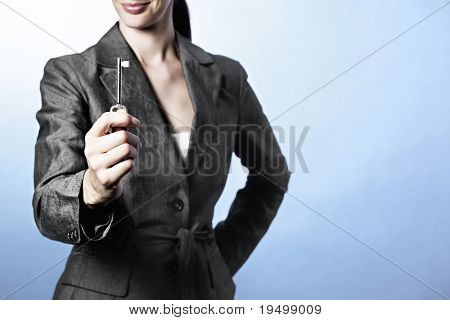 The Key to Success concept: , Portrait of business woman holding key between fingers, focus on key.