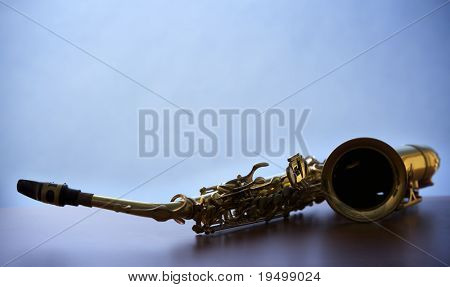 Close-up of backlit saxophone lying on wooden board with narrow focus on buttons, blue background.