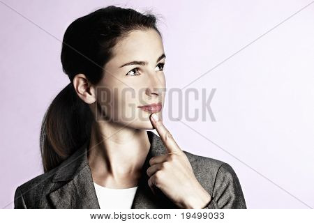 Close-up of young businesswoman thinking whilst looking upwards and holding finger against chin, isolated on pink background.