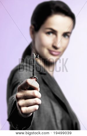 The Key to Success concept: Portrait of business woman holding key upright between fingers, focus on key, pink background.