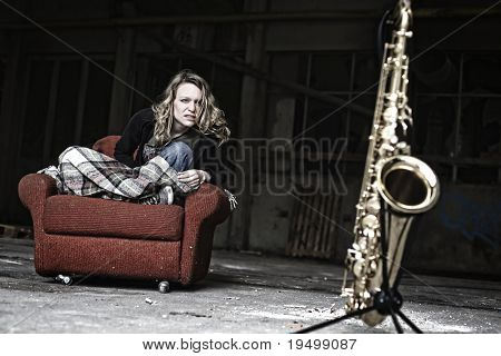 Groovy girl sitting in shabby sofa starring aggressively at saxophone in old run-down factory.