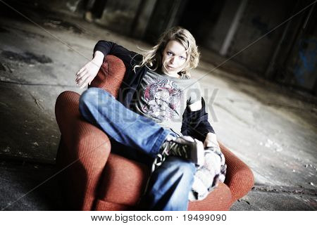 Cool girl sitting relaxed in shabby red sofa in old factory hall.