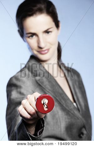 Concept: Unlocking opportunities, young attractive business woman inserting key into floating keyhole, focus on key.