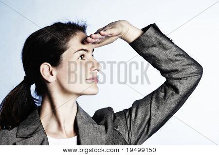 Concept: Positive business outlook. Young businesswoman looking far ahead, on light-blue background.