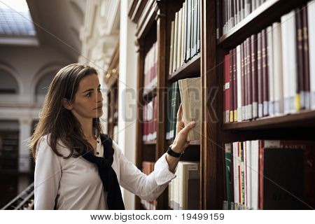 Pretty female student standing at bookshelf in old university library searching for a book.