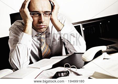 Empresário preocupado sentado na mesa de escritório com livros e artigos, sendo sobrecarregados com o trabalho completo.