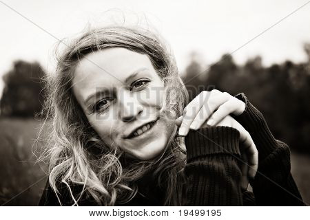 Portrait of young smiling woman sitting in the meadow, sepia toned.