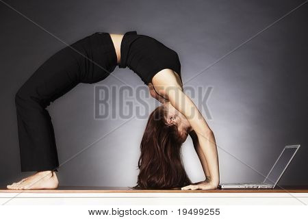 Young pretty woman in yoga wheel posture looking at laptop, backlit grey background.