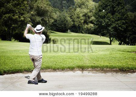 Jogador de golfe masculino jovem lascando no bunker com a floresta ao fundo.