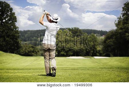 Golfe masculino jogador teeing fora bola de golfe no belo campo de golfe com floresta.
