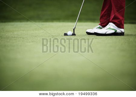 Feet of female golf player putting at green, with plenty of copy-space.