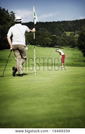 Attractive female golf player putting on green with second male player in the foreground holding the flag.