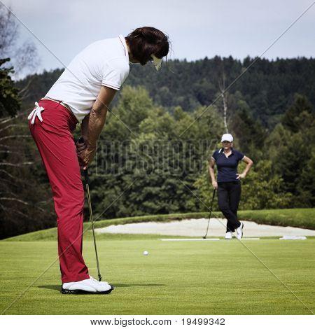 Jugador de golf femenino atractivo poniendo en verde con el segundo jugador en el fondo.