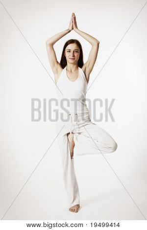 Young lady practicing yoga in tree posture (Vrikshasana) in white clothes on white background, high-key image.