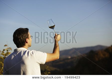 Male winemaker holding up glass of wine for checking consistency of his creation with landscape of hills and blue sky in background.