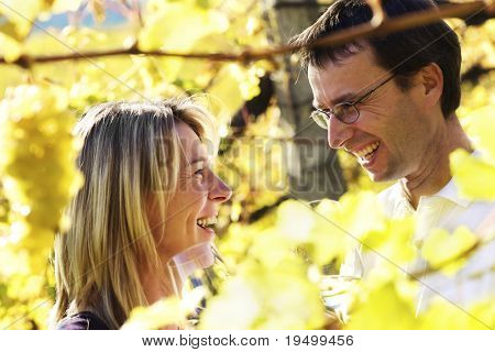 Laughing woman and man (couple) tasting wine in vineyard with blurred bunch of green grapes and vine leaves in foreground.