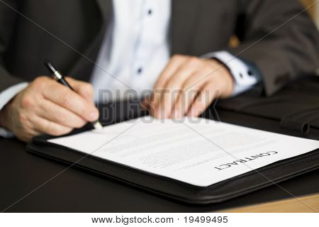 "Businessman in dark suit and blue shirt sitting in office at desk and signing a contract with shallow focus on word ""contract""."