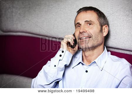 Friendly senir businessman in blue shirt sitting on sofa and talking on cell phone.